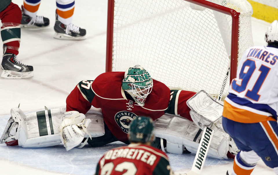Photo - Minnesota Wild goalie Josh Harding does the splits to make a save against the New York Islanders forward John Tavares during the first period of their NHL hockey game, Sunday, Dec. 29, 2013, in St. Paul, Minn. (AP Photo/Andy Clayton-King)