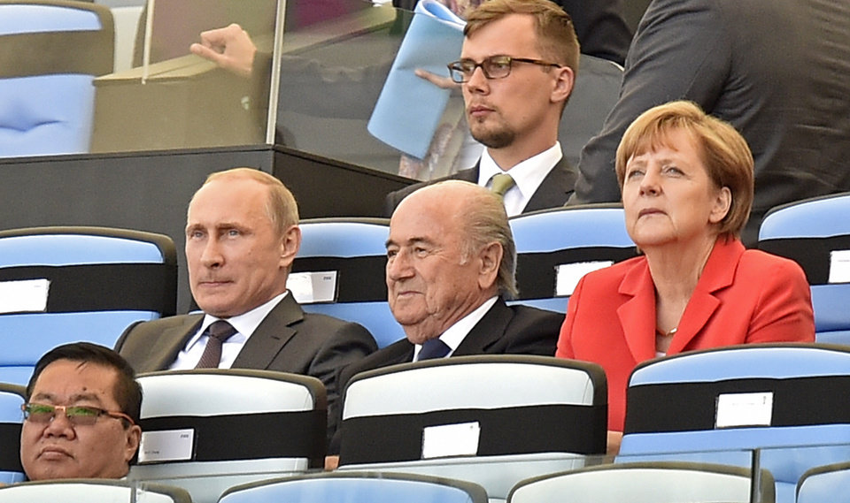 Photo - Russia's President Vladimir Putin, left, FIFA President Sepp Blatter, center, and Germany's Chancellor Angela Merkel, right, watch the opening ceremony of the World Cup final soccer match between Germany and Argentina at Maracana Stadium in Rio de Janeiro, Brazil, Sunday, July 13, 2014. (AP Photo/Martin Meissner)