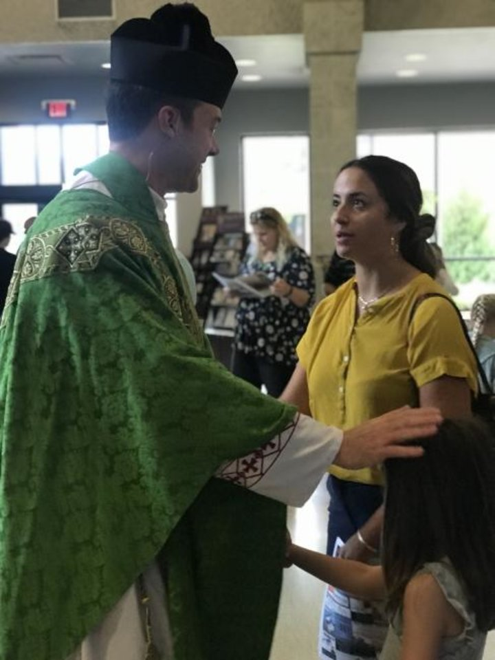 Photo -  The Rev. Adam Hamilton, pastor of St. Monica Catholic Church in Edmond, talks Sunday with parishioner Maria Cooney and her daughter Lorraine after Mass. [Carla Hinton/The Oklahoman]