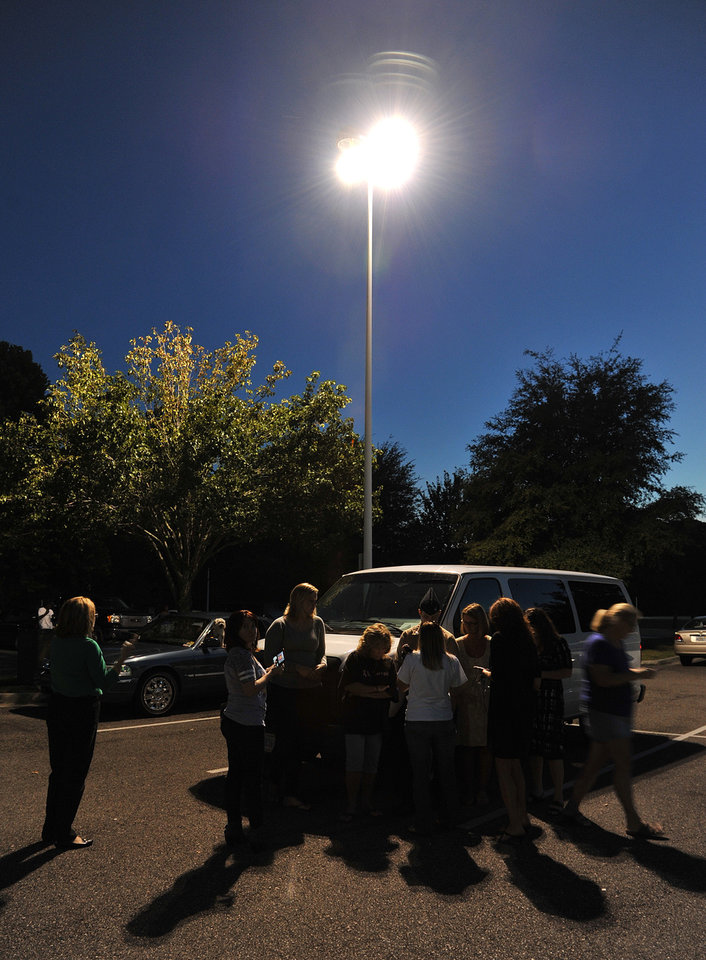 Photo - Friends and family huddle under a street light in the Jacksonville International Airport courtesy parking lot using phones to communicate with passengers stuck in the airport or in other cities Tuesday, Oct. 1, 2013, in Jacksonville, Fla. The airport was evacuated after authorities found two suspicious packages. (AP Photo/The Florida Times-Union, Bruce Lipsky)