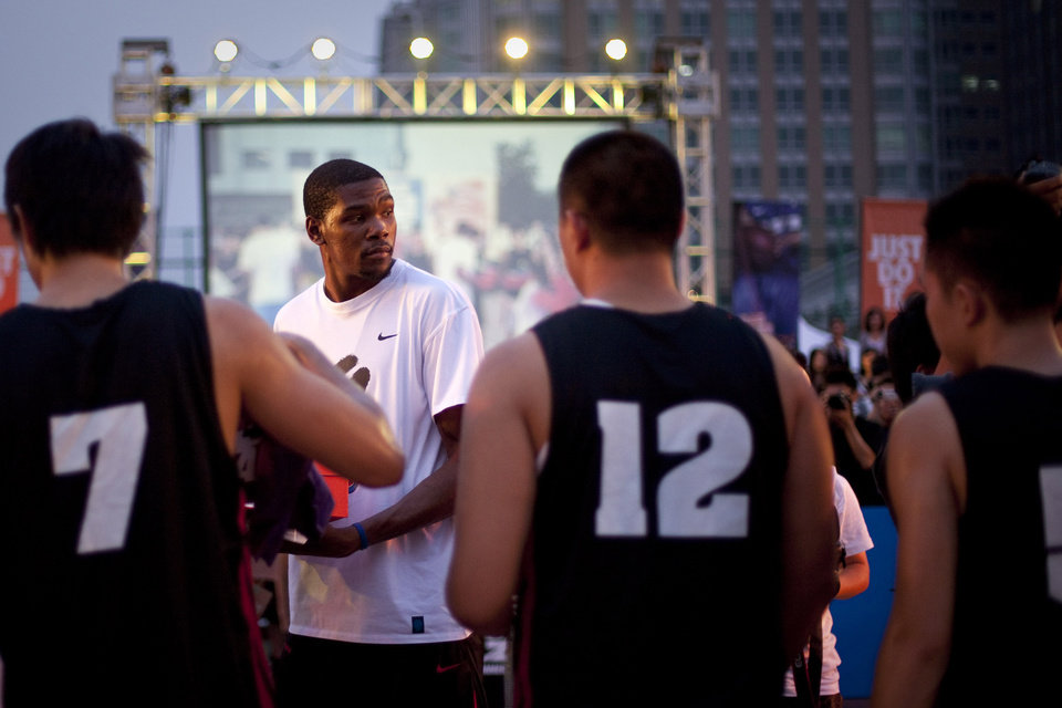 Photo - NBA Oklahoma City Thunder's Kevin Durant hands out basketball shoes to amateur players at a promotional event for sports apparel company Nike in Beijing, China, Wednesday, July 13, 2011. (AP Photo/Alexander F. Yuan) ORG XMIT: XAY106