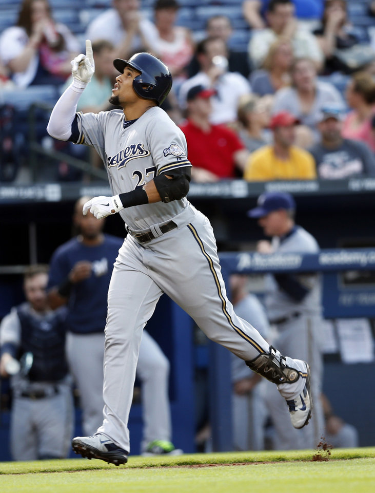 Photo - Milwaukee Brewers center fielder Carlos Gomez (27) reacts as he rounds the bases after hitting a two-run home run in the fourth inning of a baseball game Wednesday, May 21, 2014 in Atlanta. (AP Photo/John Bazemore)