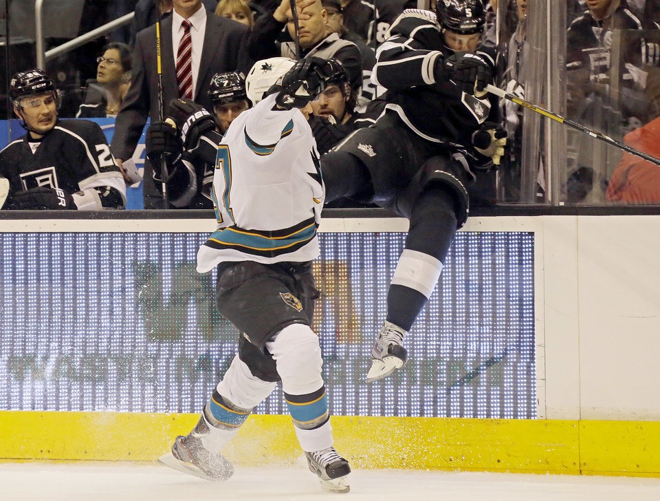 Photo - San Jose Sharks center Tommy Wingels (57) checks Los Angeles Kings defenseman Keaton Ellerby (5) into the bench in the first period of an NHL hockey game in Los Angeles Saturday, April 27, 2013. (AP Photo/Reed Saxon)