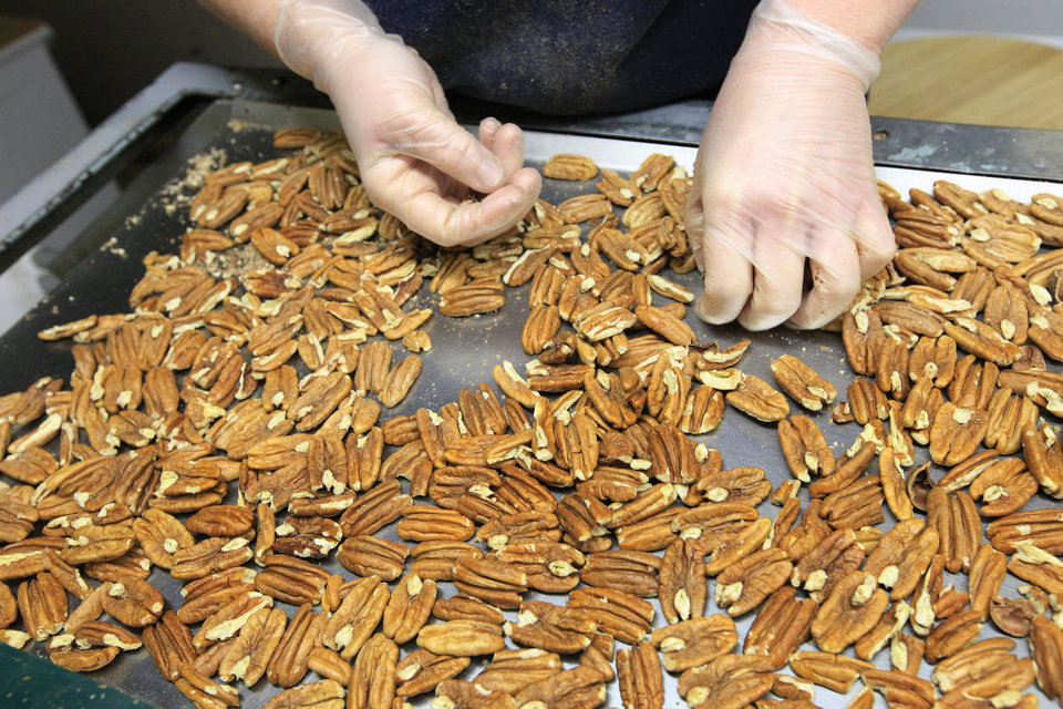 Photo - A worker sorts pecans on an inspection table at Couch Orchard in Luther Monday, Dec. 23, 2013.  Photo by Paul B. Southerland, The Oklahoman