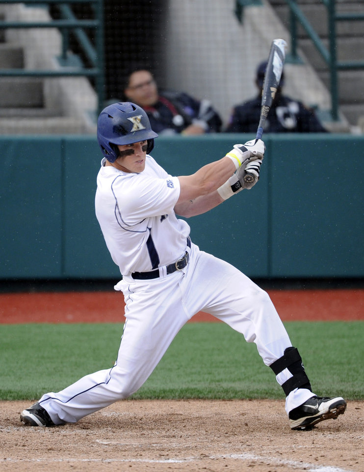 Photo - Xavier's Mitch Elliott hits an RBI-double during the third inning of an NCAA college baseball game against St. John's in the Big East tournament Friday, May 23, 2014, in New York. (AP Photo/Bill Kostroun)
