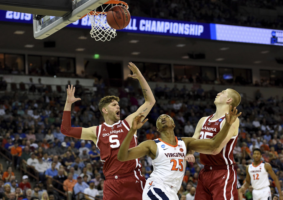 Photo - Virginia's Mamadi Diakite (25) after shooting looks for the rebound while defended by Oklahoma's Matt Freeman (5) and Brady Manek (35) during the second half of a second round men's college basketball game in the NCAA Tournament in Columbia, S.C. Sunday, March 24, 2019. (AP Photo/Richard Shiro)