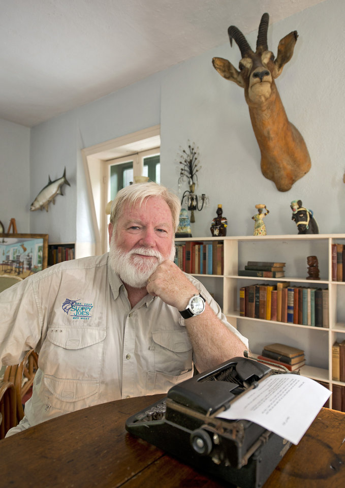 Photo - FILE - In this July 21, 2013 file photo originally provided by the Florida Keys News Bureau, Stephen Terry poses in Ernest Hemingway's one-time study at the Hemingway Home and Museum in Key West, Fla. Terry, 56, beat 125 other contestants in an Ernest Hemingway look alike contest during Key West's annual Hemingway Days festival celebrating anniversary of the author's birth. There are sites connected to Hemingway in many different locales including Florida, Cuba, Arkansas, Idaho and Illinois. (AP Photo/Florida Keys News Bureau, Andy Newman, File)