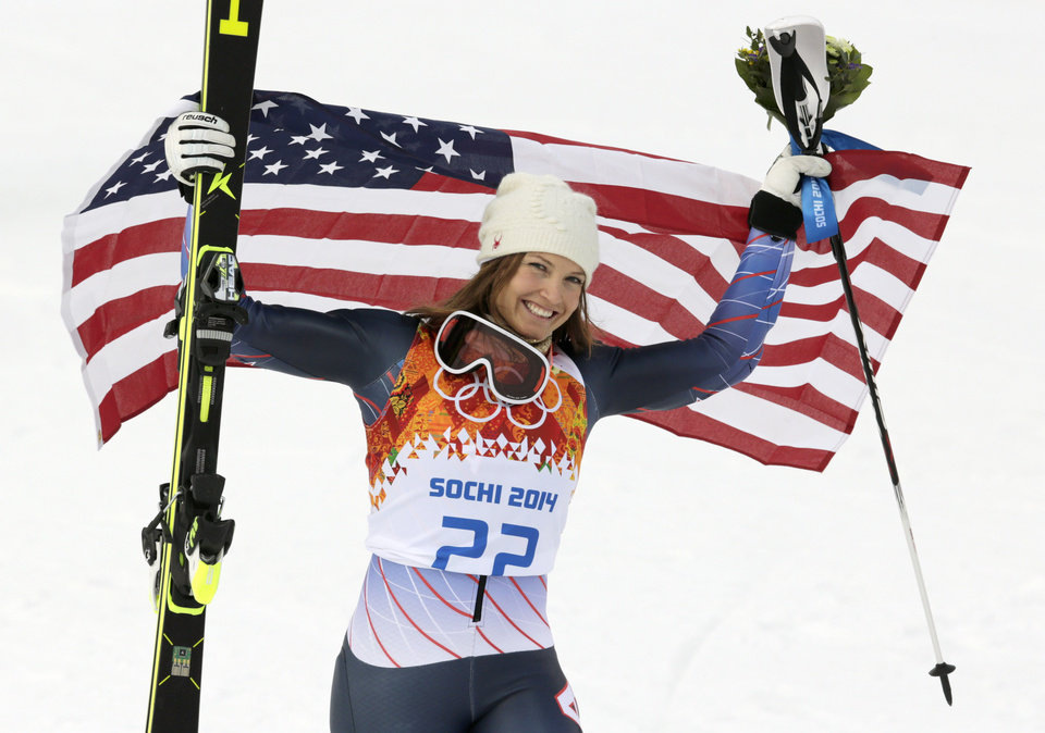 Photo - Women's supercombined bronze medalist United States' Julia Mancuso poses with the U.S. flag after a flower ceremony at the Alpine ski venue in the Sochi 2014 Winter Olympics, Monday, Feb. 10, 2014, in Krasnaya Polyana, Russia.(AP Photo/Charles Krupa)