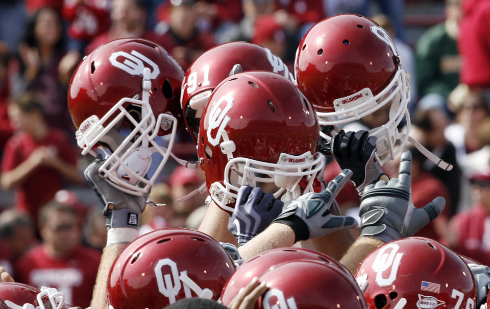 Photo - Sooners raise their helmets before the college football game between The University of Oklahoma Sooners (OU) and the Baylor Bears at the Gaylord Family-Oklahoma Memeorial Stadium on Saturday, Oct. 10, 2009, in Norman, Okla.