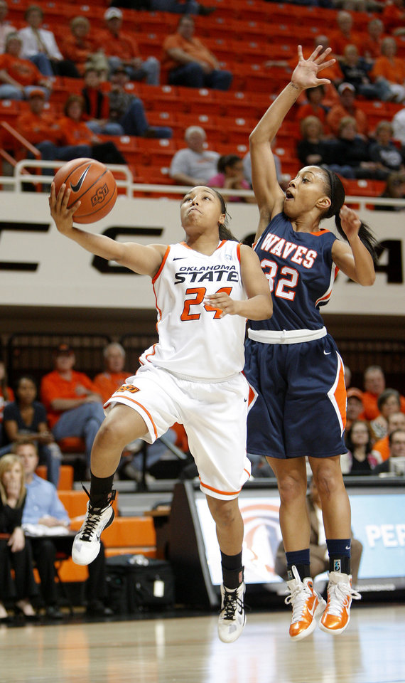 Photo - OSU's Carissa Crutchfield (24) goes past Pepperdine's Lauren Bell (32) during a first-round NIT women's college basketball game between Oklahoma State University (OSU) and Pepperdine at Gallagher-Iba Arena in Stillwater, Okla., Wednesday, March 16, 2011. Photo by Bryan Terry, The Oklahoman