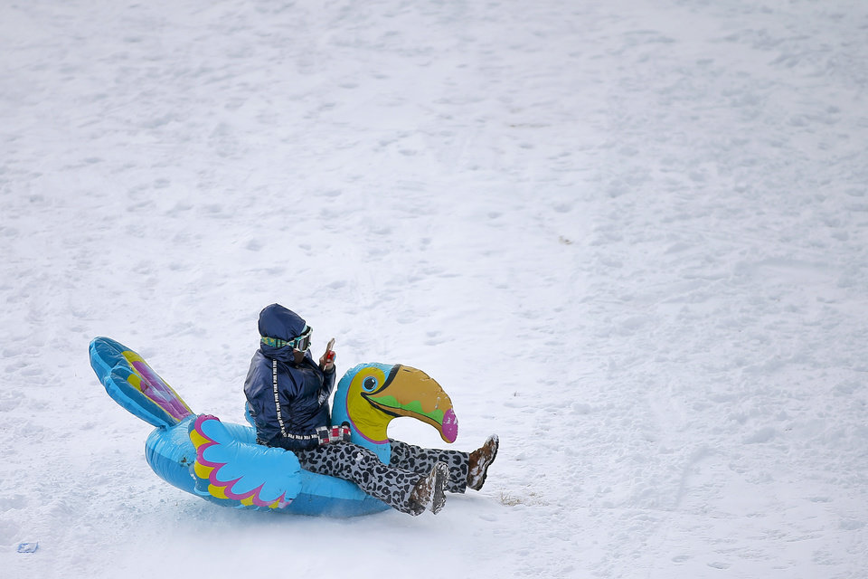 Photo - Megan Kozart slides down a hill on an inflatable bird along W Hefner Road in Oklahoma City after a winter storm dropped another layer of snow in Oklahoma City, Wednesday, Feb. 17, 2021. [Bryan Terry/The Oklahoman]