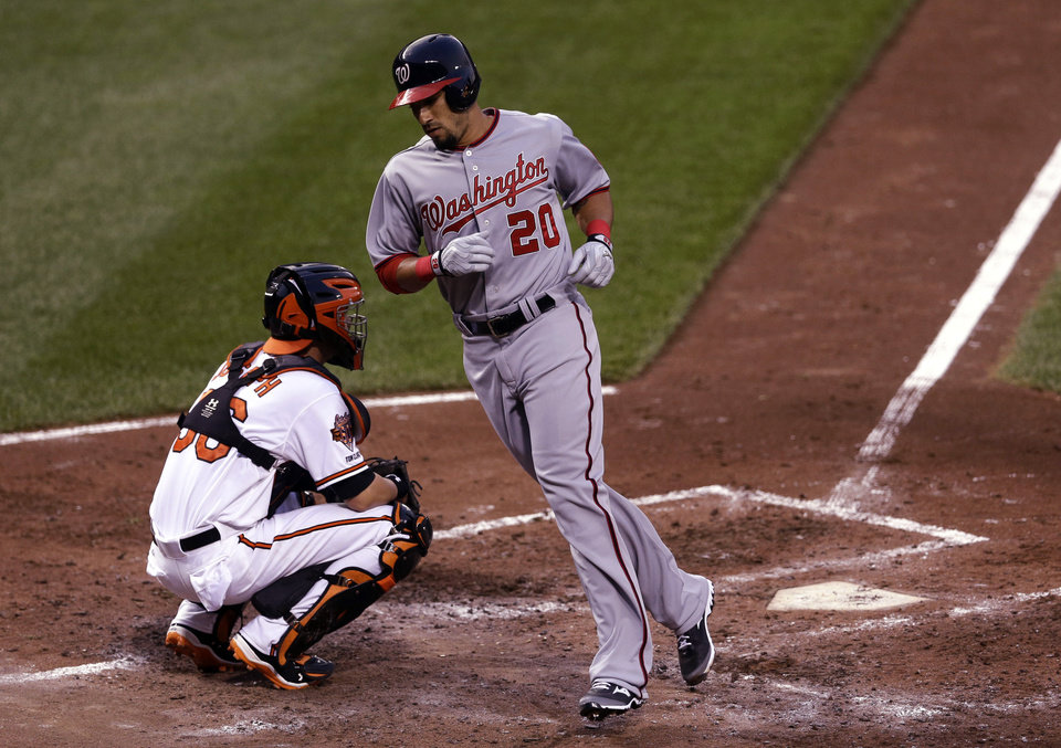 Photo - Washington Nationals' Ian Desmond rounds toward the dugout after crossing home plate in front of Baltimore Orioles catcher Caleb Joseph after hitting a solo home run in the fourth inning of an interleague baseball game, Wednesday, July 9, 2014, in Baltimore. (AP Photo/Patrick Semansky)
