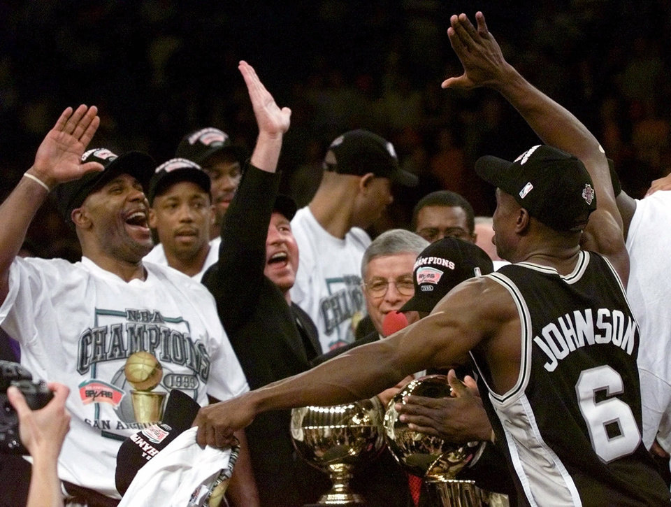 Photo - San Antonio Spurs' Avery Johnson (6) and teammate Mario Elie, left, throw up their hands for a high-five after defeating the New York Knicks 78-77 in Game 5 of the 1999 NBA Finals to clinch the championship Friday, June 25, 1999, at New York's Madison Square Garden. (AP Photo/Kathy Willens)
