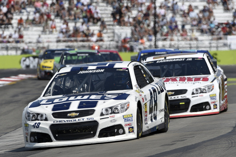 Photo - Jimmie Johnson (48) leads Dale Earnhardt Jr. (88) and others during a NASCAR Sprint Cup Series auto race at Watkins Glen International, Sunday, Aug. 10, 2014, in Watkins Glen N.Y. (AP Photo/Derik Hamilton)