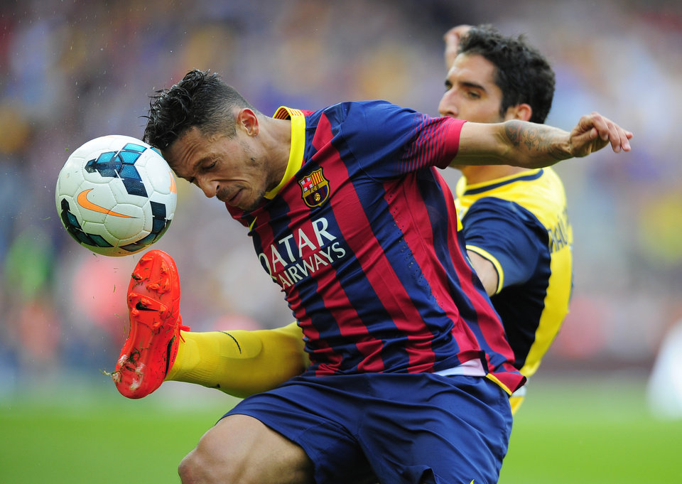 Photo - Barcelona's Adriano Correia, from Brazil, left, heads the ball challenged by Atletico's Raul Garcia during a Spanish La Liga soccer match between FC Barcelona and Atletico Madrid at the Camp Nou stadium in Barcelona, Spain, Saturday, May 17, 2014. (AP Photo/Manu Fernandez)