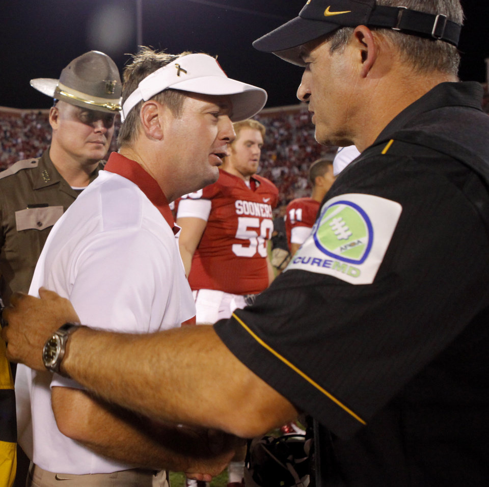 Photo - Oklahoma coach Bob Stoops meets with Missouri coach Gary Pinkel after the college football game between the University of Oklahoma Sooners (OU) and the University of Missouri Tigers (MU) at the Gaylord Family-Memorial Stadium on Saturday, Sept. 24, 2011, in Norman, Okla. Photo by Bryan Terry, The Oklahoman