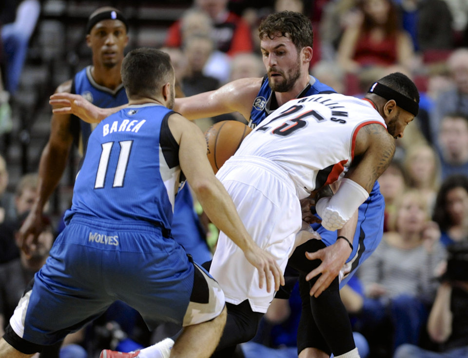 Photo - Minnesota Timberwolves' Kevin Love (42) strips the ball from Portland Trail Blazers' Mo Williams (25) during the first half of an NBA basketball game in Portland, Ore., Sunday Feb. 23, 2014. (AP Photo/Greg Wahl-Stephens)