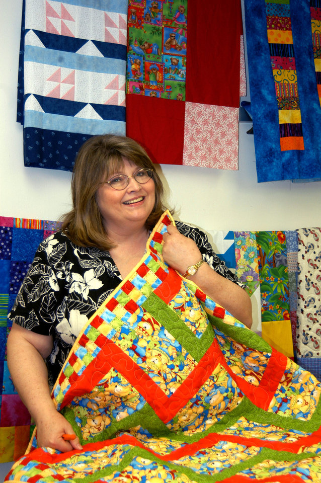 Rose State College's Associate Dean and Professor of Sociology is surrounded by the many quilts students have quilted in the quilting classes on campus.  Many of the quilts have been donated to various charities in the community<br/><b>Community Photo By:</b> Steve Reeves<br/><b>Submitted By:</b> Donna, Choctaw