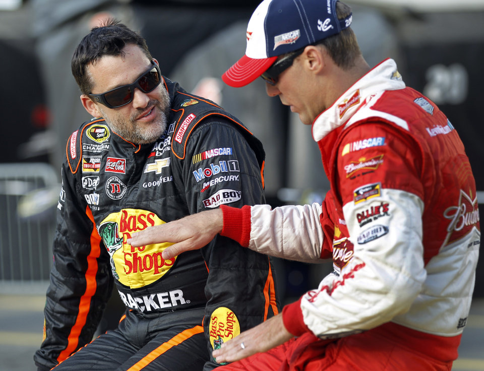 Photo - FILE - In this May 22, 2014, file photo, Tony Stewart, left, talks with Kevin Harvick before qualifying for a NASCAR Sprint Cup series auto race at Charlotte Motor Speedway in Concord, N.C. Stewart is skipping a second straight Sprint Cup race, and it is not clear when the NASCAR star might return after he struck and killed a driver at a dirt-track race in New York last weekend. (AP Photo/Terry Renna, File)
