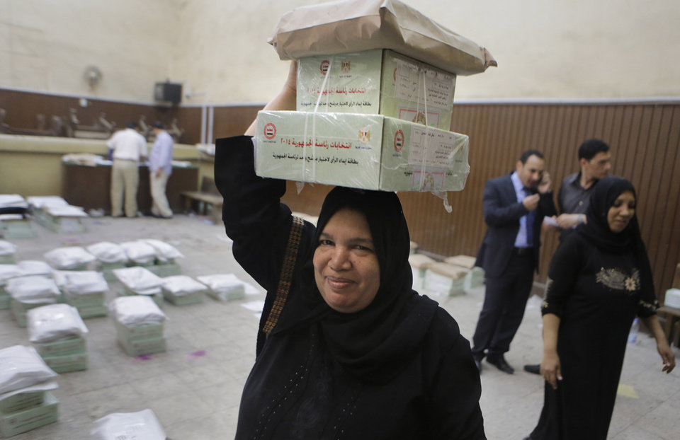 Photo - An Egyptian worker carries boxes of ballots at the Giza courthouse in Cairo, Egypt, Sunday, May 25, 2014, a day before the country's presidential elections. Egypt's interim President Adly Mansour has urged Egyptians to come out and vote in this week's presidential election, saying the vote will shape the nation's future. (AP Photo/Amr Nabil)