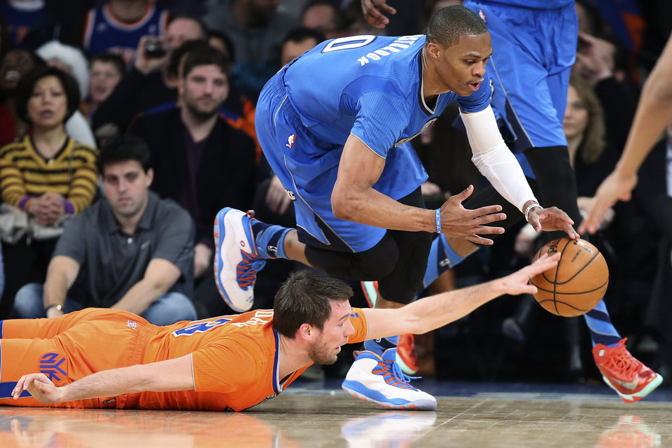 Oklahoma City Thunder guard Russell Westbrook (0) and New York Knicks guard Beno Udrih (18) scramble for a loose ball during the first half of an NBA basketball game at Madison Square Garden, Wednesday, Dec. 25, 2013, in New York. The Thunder won 123-94. (AP Photo/John Minchillo)