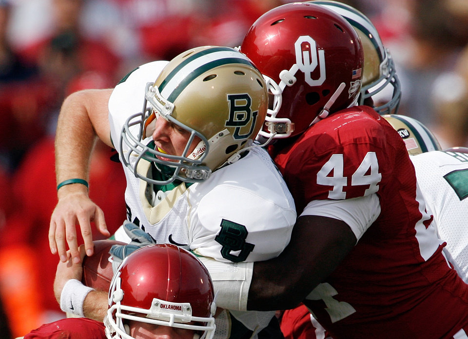 Photo - Quarterback Nick Florence is sacked by Jeremy Beal during the first half of the college football game between The University of Oklahoma Sooners (OU) and the Baylor Bears at the Gaylord Family-Oklahoma Memeorial Stadium on Saturday, Oct. 10, 2009, in Norman, Okla.