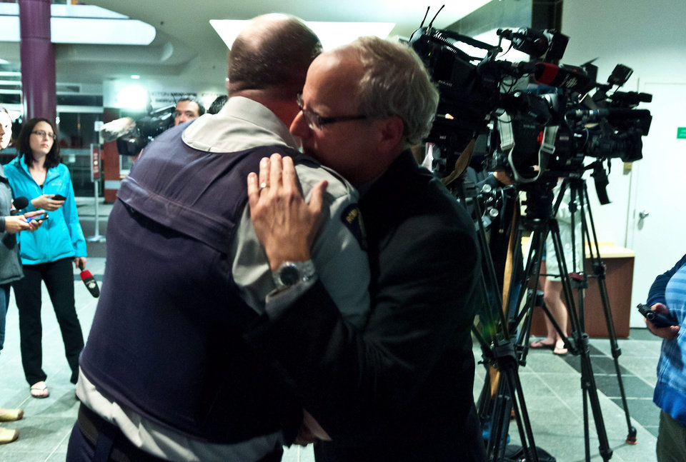 Photo - Royal Canadian Mounted Police officer officer Damien Theriault, left, and Mayor George LeBlanc hug after addressing the media during a late press conference at City Hall in Moncton, New Brunswick on Wednesday June 4, 2014. Three police officers were shot dead and two others injured in a rare case of gun violence in the east coast Canadian province of New Brunswick, officials said. (AP Photo/The Canadian Press, Marc Grandmaison)