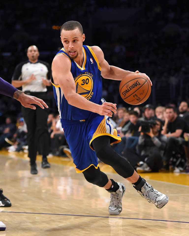 Photo - Golden State Warriors guard Stephen Curry drives to the basket during the second half of an NBA basketball game against the Los Angeles Lakers, Friday, April 11, 2014, in Los Angeles. The Warriors won 112-95. (AP Photo/Mark J. Terrill)