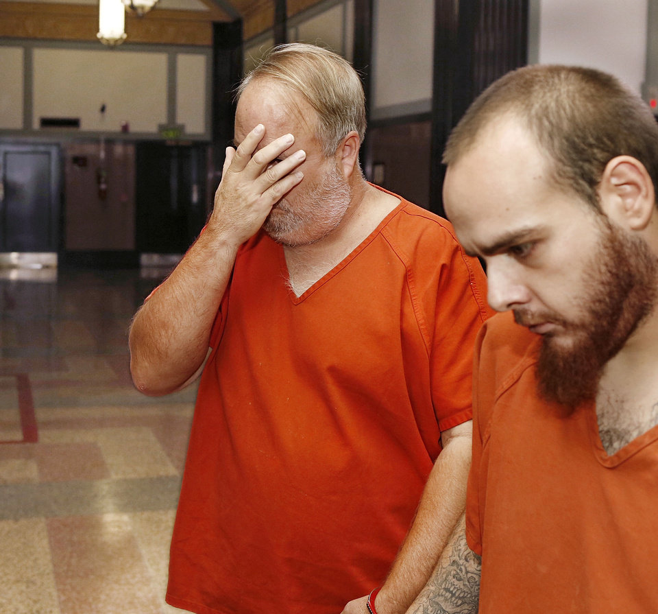 Photo - David Bloebaum, accused of killing a man Sept. 28 in a road rage incident in the parking lot of a Target store in northwest Oklahoma City, appeared Wednesday before District Judge Kenneth Watson in the Oklahoma County Courthouse.  He is shown shielding his face from cameras as he is led into the courtroom. Photo by Jim Beckel, The Oklahoman  Jim Beckel