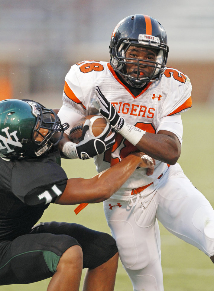 Donovan Roberts (28) tries to shed tackler D.J. Hicks (21) as the Norman High School Tigers play the Norman North Timberwolves at Gaylord Family-Oklahoma Memorial Stadium on Thursday, Sept 1, 2011, in Norman, Okla.   Photo by Steve Sisney, The Oklahoman