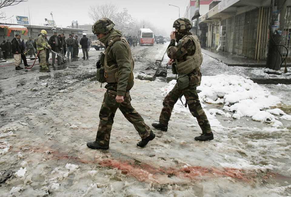 French soldiers with the NATO- led forces walk past blood stained snow at the scene of a suicide attack in Kabul, Afghanistan, Wednesday, Feb. 27, 2013. A man wearing a black overcoat and carrying an umbrella as a shelter against the heavy snow crossed a street in the Afghan capital early Wednesday morning toward an idling bus filled with Afghan soldiers, where he laid down and wiggled underneath. Then he exploded, engulfing the undercarriage of the bus in flames. (AP Photo/Ahmad Jamshid)