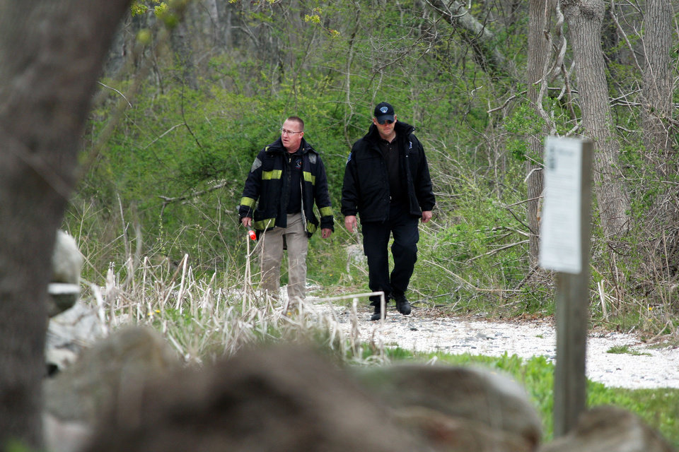 Photo - Massachusetts State Police walk out of the woods of The Smith Neck Farm in Dartmouth, Mass. on Friday, May 3, 2013 as federal, state and local authorities on Friday searched the woods near the UMass-Dartmouth campus as part of the marathon investigation. (AP Photo/The Standard-Times, John Sladewski)