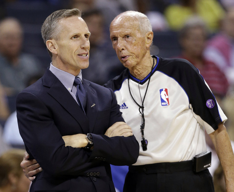 Photo - Charlotte Bobcats head coach Mike Dunlap, left, talks with referee Dick Bavetta, right, during the first half of an NBA basketball game against the Cleveland Cavaliers in Charlotte, N.C., Wednesday, April 17, 2013. (AP Photo/Chuck Burton)