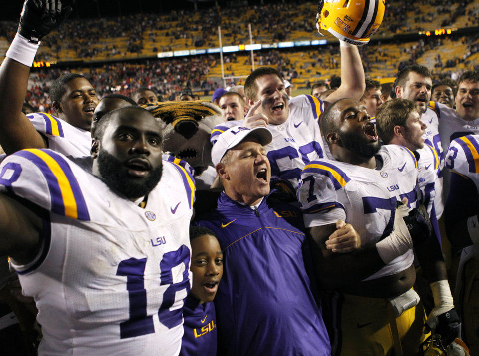 Photo -   LSU head coach Les Miles sing the school anthem with his team, including defensive tackle Bennie Logan (18) and defensive tackle Josh Downs (77) in the second half of their NCAA college football game against Mississippi in Baton Rouge, La., Saturday, Nov. 17, 2012. LSU won 41-35. (AP Photo/Gerald Herbert)