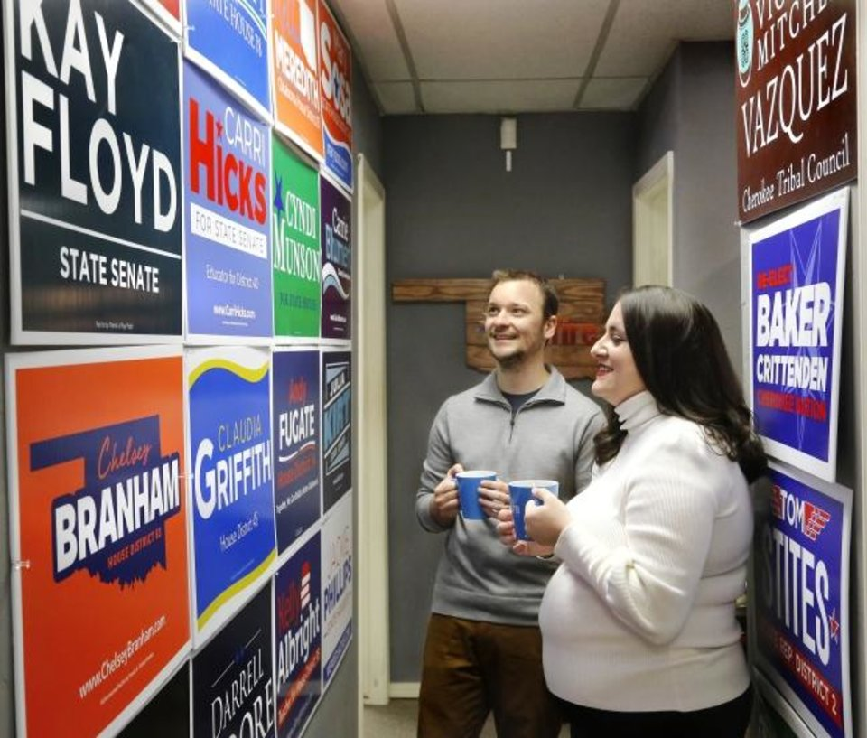 Photo -  Joe Hartman and Cassi Peters, co-owners of Skyfire Media, look Friday at the campaign signs for some of the candidates they represented.  [Jim Beckel/ The Oklahoman]