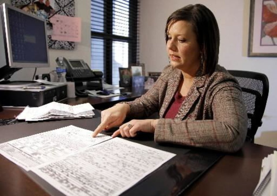 Courtney McClure looks over an accident report and medical bills in her Oklahoma City office, Wednesday, Feb. 4, 2009. McClure was in an accident with an  uninsured motorist in 2006. PHOTO BY BRYAN TERRY