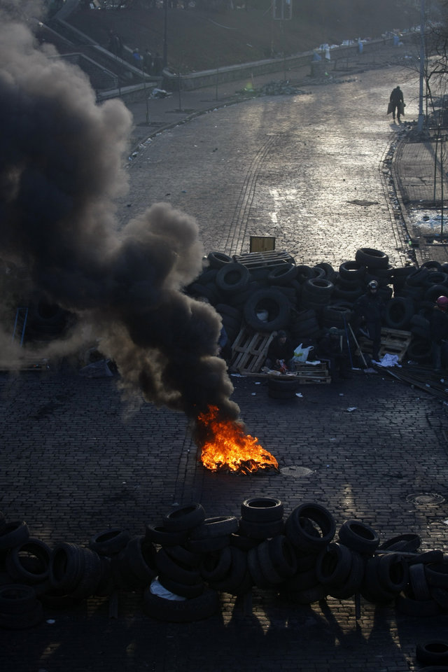 Photo - A fire burns on a barricade at Independence Square in Kiev, Ukraine, Friday, Feb. 21, 2014. Ukraine's presidency said Friday that it has negotiated a deal intended to end battles between police and protesters that have killed scores and injured hundreds, but European mediators involved in the talks wouldn't confirm a breakthrough. (AP Photo/ Marko Drobnjakovic)