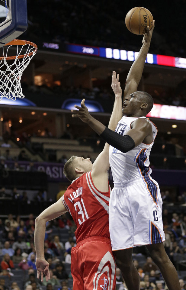 Charlotte Bobcats\' Bismack Biyombo, right, shoots over Houston Rockets\' Cole Aldrich, left, during the first half of an NBA basketball game in Charlotte, N.C., Monday, Jan. 21, 2013. (AP Photo/Chuck Burton)