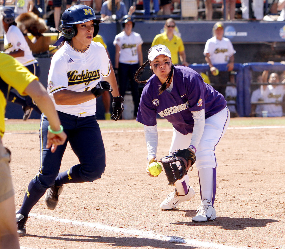 Photo - Washington Huskies pitcher Bryana Walker fields a ground ball and tosses it to first base in the Women's College World Series elimination game versus Michigan. The Washington Huskies would won 4-1 on June 2, 2013. Photo by KT KING, The Oklahoman