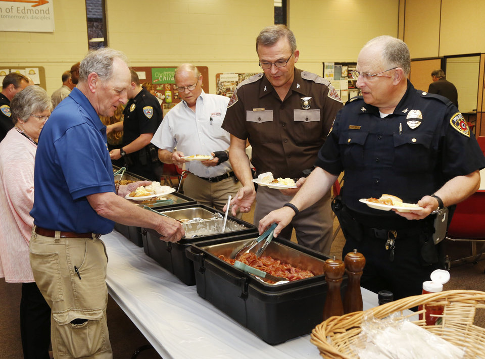 Photo -  Oklahoma Highway Patrol Chief Ricky Adams, second from right, law enforcement officers and residents attend a prayer breakfast in Edmond. [PHOTO BY PAUL HELLSTERN, THE OKLAHOMA]