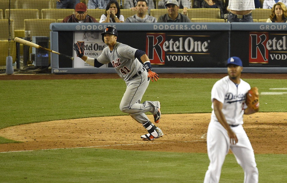 Photo - Detroit Tigers' Victor Martinez, left, tosses his bat as he hits a solo home run as Los Angeles Dodgers relief pitcher Kenley Jansen, right, looks on during the 10th inning of a baseball game, Wednesday, April 9, 2014, in Los Angeles. (AP Photo/Mark J. Terrill)