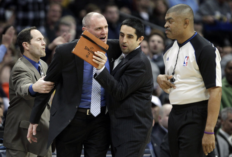 Photo - Dallas Mavericks assistant coaches Monte Mathis, left, and Kaleb Canales, third from left, try to separate coach Rick Carlisle from referee Tony Brothers, right, moments before Carlisle was issued a second technical foul and ejected in the second quarter of an NBA basketball game in Denver on Saturday, Nov. 23, 2013. (AP Photo/Joe Mahoney)