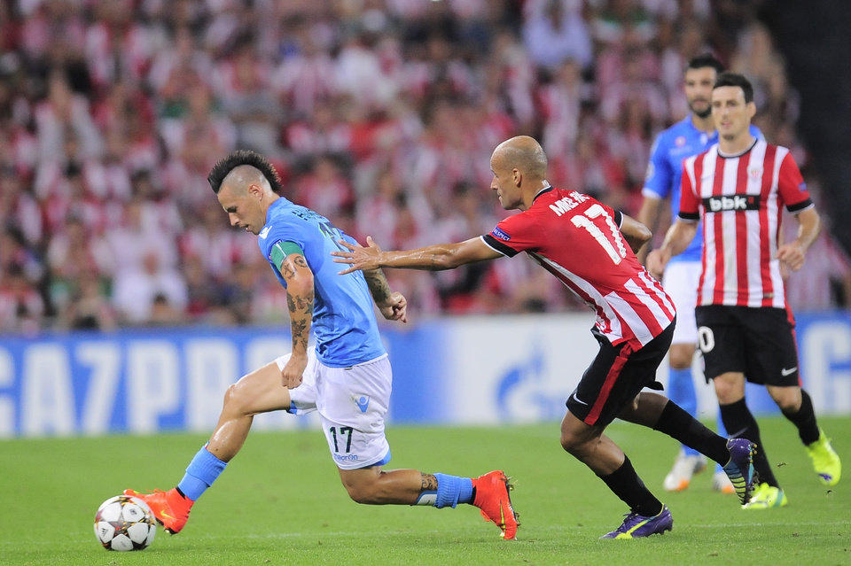 Photo - Athletic Bilbao's Mikel Rico, right, runs with the ball in front of SSC Napoli's Marek Hamsik, during their Champions League playoff second leg soccer match, at San Mames stadium in Bilbao, northern Spain, Wednesday, Aug. 27, 2014. (AP Photo/Alvaro Barrientos)