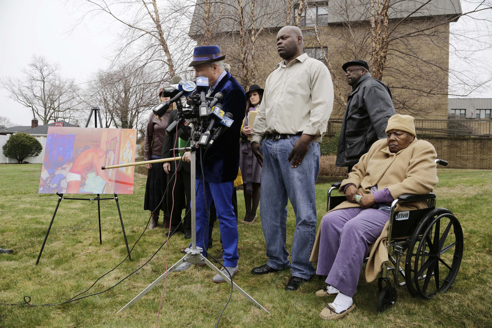 Photo - Bernice Youngblood, right, 85, a resident of the East Neck Nursing and Rehabilitation Center, listens as her attorney, John Ray, left, points to a photograph with his cane during a news conference on the lawn of the nursing home, Tuesday, April 8, 2014 in West Babylon, N.Y. The photograph reportedly shows a male exotic dancer performing for Youngblood and other patients at the facility. With Youngblood are her sons, Darrell, center, and Franklin, second right.  (AP Photo/Mark Lennihan)
