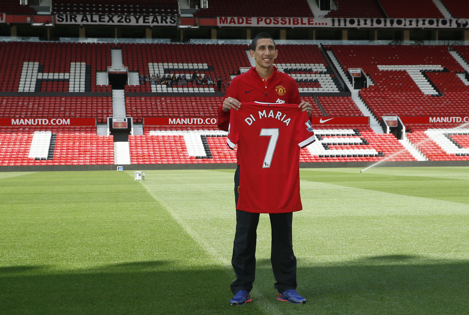 Photo - Manchester United's new player Angel Di Maria poses for photographers holding his new shirt, at Old Trafford Stadium in Manchester, England, Thursday, Aug. 28, 2014. Manchester United have signed winger Angel Di Maria from Real Madrid for a British record transfer fee of £59.7m. The Argentine winger had a medical in Manchester on Tuesday and has signed a five-year deal. (AP Photo/Alastair Grant)