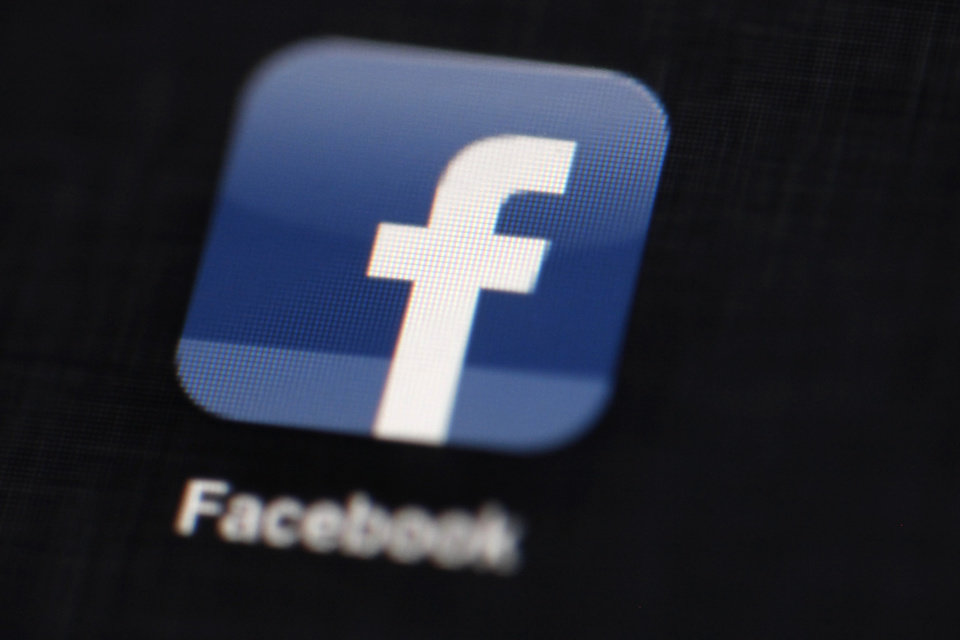 Photo - FILE - This May 16, 2012 file photo shows the Facebook logo displayed on an iPad in Philadelphia. More Americans check Facebook daily than read the Bible every day. Much more, by more than a three-to-one margin. As Facebook celebrates its 10th anniversary, the numbers it generates are epic. Facebook says worldwide it has 757 million daily active users. Of those 19 percent are in the U.S. and Canada, so that's more than 143 million people checking Facebook daily in America. (AP Photo/Matt Rourke, File)