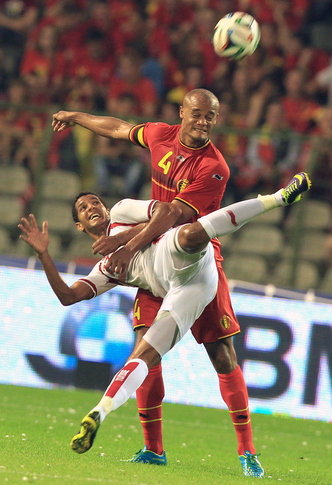 Photo - Tunisia's Issam Jemaa, left, is challenged by Belgium's Vincent Kompany, during a friendly soccer match at the King Baudouin stadium in Brussels, Saturday, June 7, 2014.  Belgium will play against South Korea, Russia and Algeria in Group H of the World Cup 2014 in Brazil. (AP Photo/Yves Logghe)