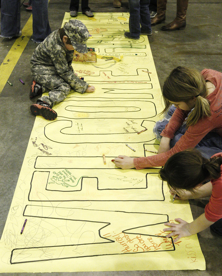 """Colten Roberts, left, age four, Gabby Kissner, center, age 10 and Kayla Livecy, right, age six, draw on a """"Welcome Home"""" sign at a ceremony for the return from Afghanistan and Kuwait of 130 members of the 45th Infantry Brigade Combat Team Soldiers of the Oklahoma National Guard,in Oklahoma City, Saturday, March 3, 2012. (AP Photo/Sue Ogrocki) ORG XMIT: OKSO102"""