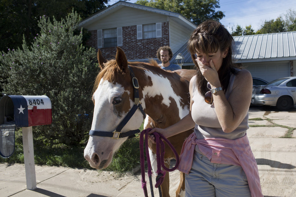 Photo - Divy Nelson stands with her horse, Amala, as she waits for an update on the status of 12 missing horses, one of which is hers, that were displaced from the same ranch after heavy rains flooded parts of the neighborhood around Onion Creek on Thursday Oct. 31, 2013 in Austin, Texas. The National Weather Service said more than a foot of rain fell in Central Texas. (AP Photo/ Tamir Kalifa)