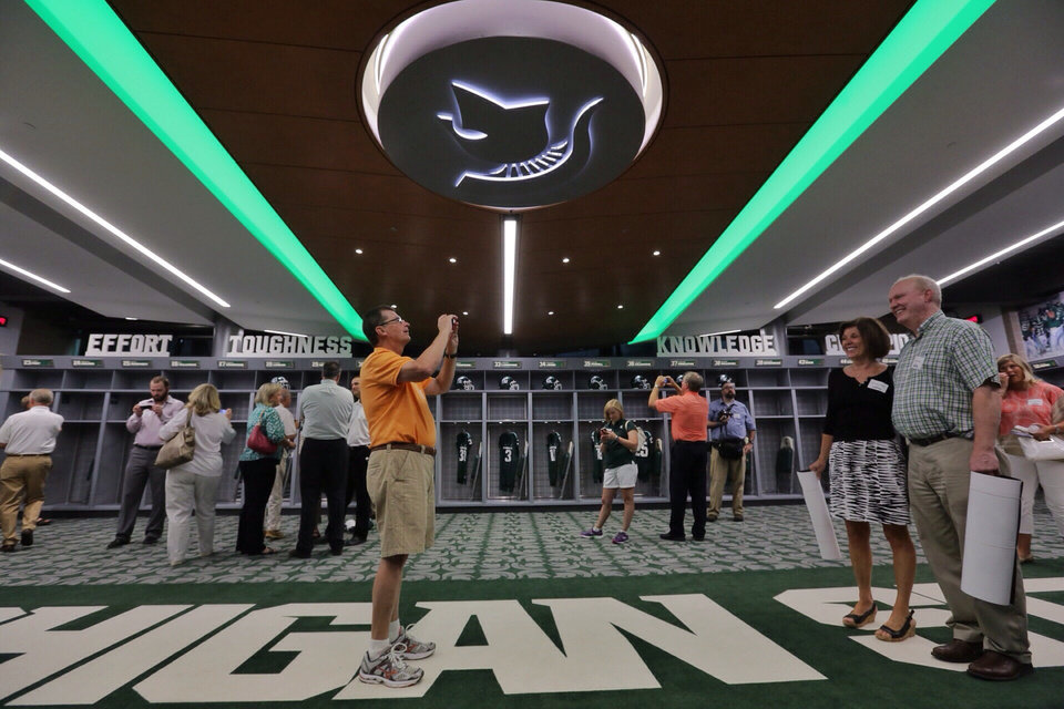 Photo - In this Monday, Aug. 25, 2014, photo, Ed Helble, of Okemos, takes a photo of his wife, Charlene, and Rich Pinke, also of Okemos, during a tour of the new North End Zone Complex renovations at Spartan Stadium in East Lansing on the Michigan State Campus. (AP Photo/Detroit Free Press, Ryan Garza)  DETROIT NEWS OUT, TV OUT, INTERNET OUT, MAGS OUT, NO SALES, MANDATORY CREDIT DETROIT FREE PRESS